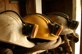 Three dirty, worn mine helmets on a shelf