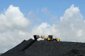 front loader dumping coal over a mountain of coal