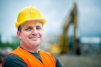 Coal worker standing in front of a large piece of machinery with the background blurred