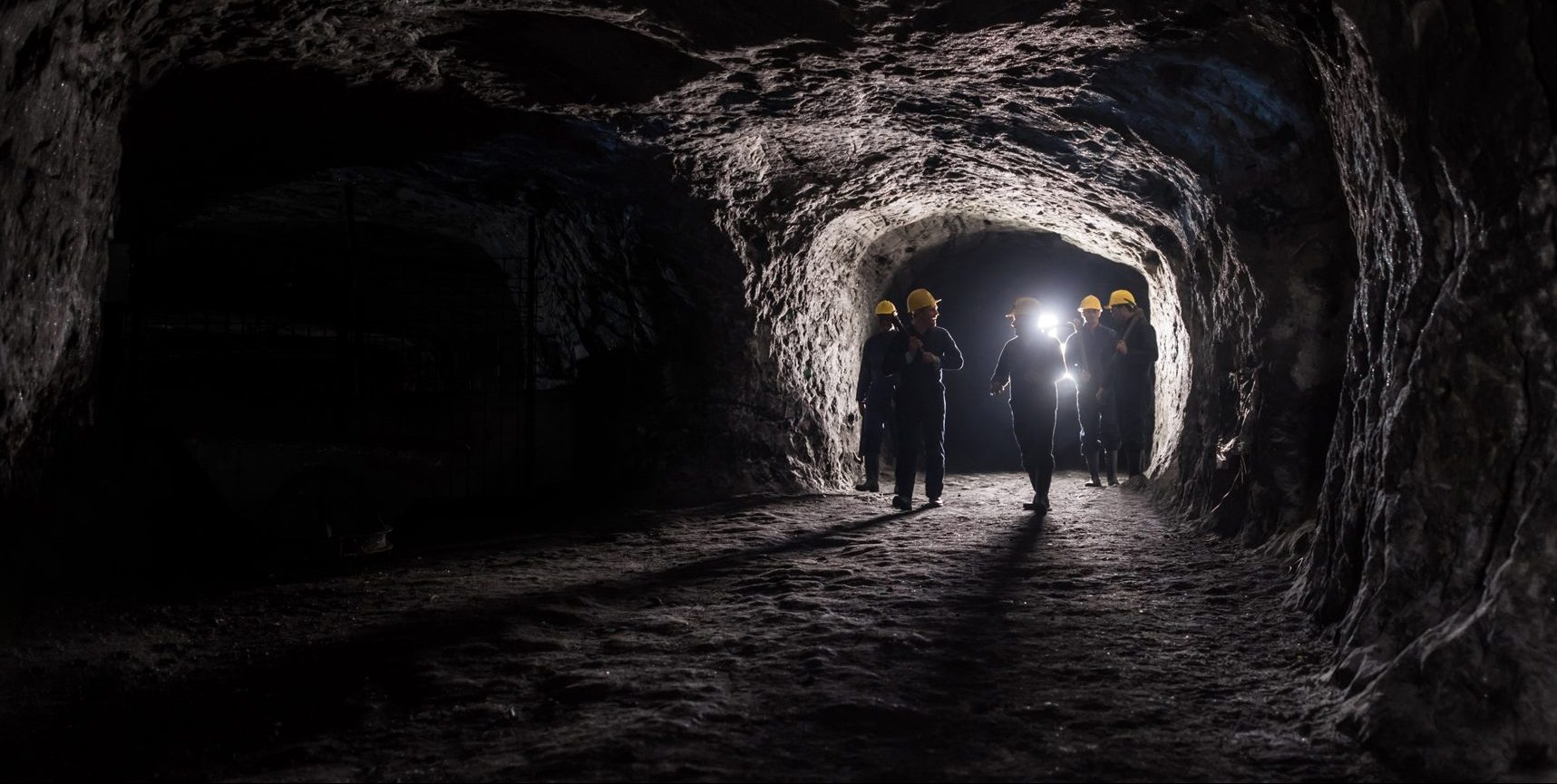 Coal miners talking and walking through a coal mine